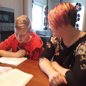 Tonårig son med matematikbok och sin mamma