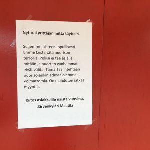 en skylt med text på finska om att företaget är irriterade över ungdomar och besvikna på polisen.
