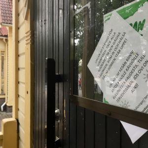 En dörr på en gul byggnad med lappar i fönstret där det står att det är stängt.