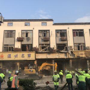 Pelastustyöntekijät raivaavat kaasuräjähdyksen jälkiä Itä-Kiinassa lapiolla ja risuluudilla.