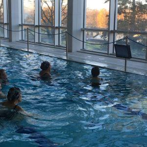 Ihmisiä uima-altaassa jumppaamassa. Ohjeet tulevat altaan reunalle kiinnitetyltä näytöltä.