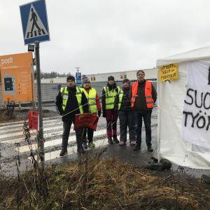 Lakossa olevia Postin työntekijöitä Tampereen postikeskuksen portilla.