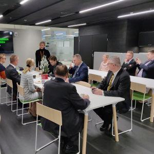 Kuvassa LUT-yliopiston tiedotustilaisuuteen osallistuneita henkilöitä. Taustalla seisoo yliopiston hallituksen varapuheenjohtaja Teresa Kemppi-Vasama.