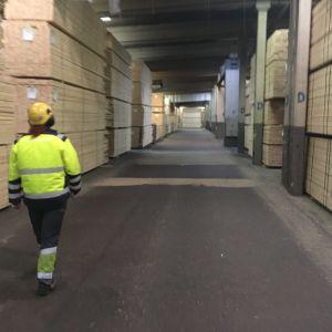 Työntekijä kävelee Versowoodin liimapuupalkkitehtaan puuvarastossa Heinolassa