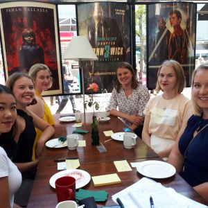 kuusi nuorta naista istuu kesäisissä vaatteissa ravintolapäydässä ja katsoo hymyillen kameraan