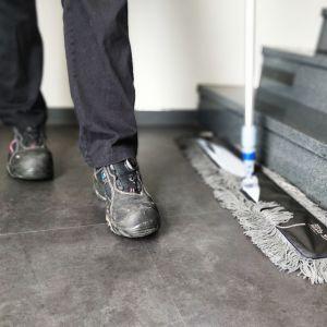 Kuvassa siivoojan jalat ja moppi.