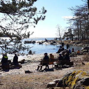 Många människor på sandstranden på Drumsö varav en del sitter på parkbänkar