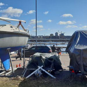 Upptagen segelbåt och andra båtar under presenning i småbåtshamn i Helsingfors.