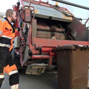 Jäteautonkuljettaja Rami Saari tyhjentää biojäteastiaa