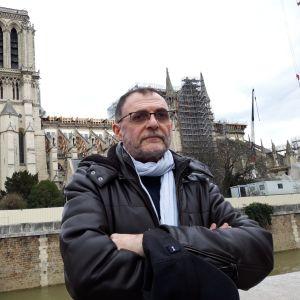 Organisten Yves Castagnet står vid Seinefolden. I bakgrunden syns ruinerna av Notre Dame.