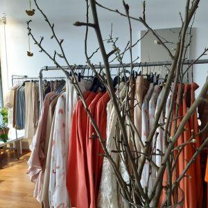 Vårkläder hänger på galgar i affär och en vas med äppelkvistar i knopp ståpr i förgrunden.