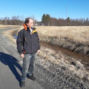 Juhani Hannila står och tittar ut över den åker som ska bli träsk i Kyrklunden i Karleby.