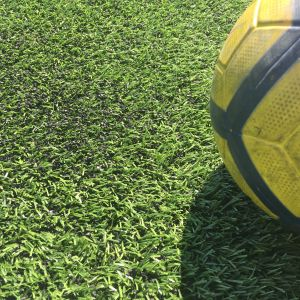 Jalkapallo tekonurmikentällä lähikuvassa.