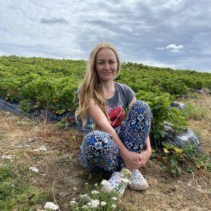 Milana Luzina istuu mansikkapellon laidalla.