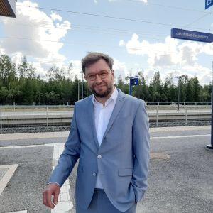 Man med kostym står på järnvägsstation.