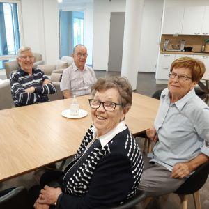 Fyra personer sitter vid ett bord.