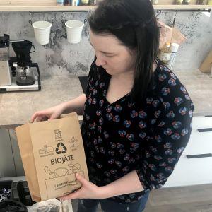 Mari Kivelä asettelee biojätepussia paikoilleen keittiössä