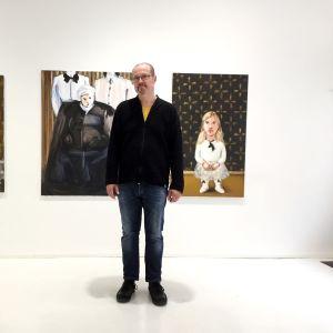 Konstnär står framför en serie målningar.