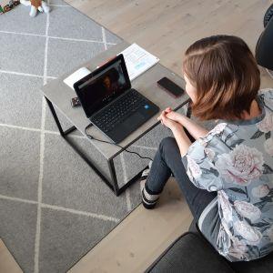 Ung person följer med undervisning via dator.
