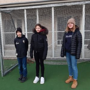 En pojke och två flickor står framför ett fotbollsmål på Åshöjdens skolgård och tittar in i kameran.