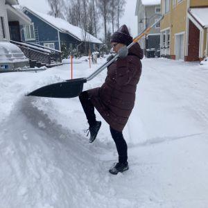 nainen siirtää lumikolalla lunta lumikasaan