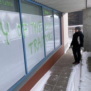 Oulun vihreän kunnallisjärjestön puheenjohtaja Aino-Kaisa Manninen katsoo vihreiden toimiston hakaristein ja uhkauksin töhrittyjä ikkunoita.Nainen katsoo