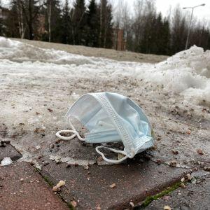 Kadulle heitetty kasvomaski Helsingissä.