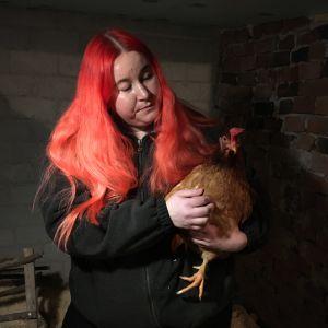 Nainen pitää sylissään kanaa