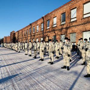 Rekryter i snödräkter står uppradade mot en rödtegelbyggnad.