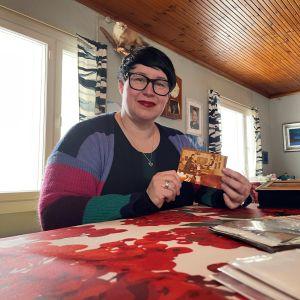 Kati Rita selailee vanhoja kuvia pirtin pöydän ääressä Ristijärvellä ja esittelee yhtä niistä kameralle.