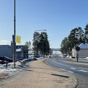 Paltamon kylänraitti jonka varressa S-market ja kaukana horisontissa Oulujärvi.