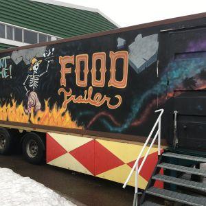 Graffitein koristeltu puoliperävaunu, jonka sisään on rakennettu keittiötila.