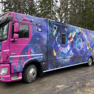 Kirjastoauto Kosmos avaruudessa mutkitteleva kirjapino kyljessään on pysäköitynä Tampereen Tasanteen kirjastoauton pysäköintipaikalle.