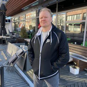Ravintolayrittäjämies seisoo terassilla ja katsoo kameraan.