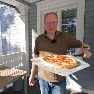 Kotikokki Juha Sivonen esittelee juuri uunista otettua pizzaa.