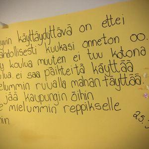 kirjoitettu lappu lastenkodin seinällä