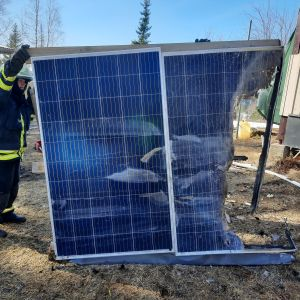 Pelastuslaitoksen työntekijä pitelee palanutta aurinkopaneelia.