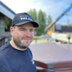 Himospaljut yrityksen toimitusjohtaja Kalle Järvelä on kannellisen paljun edessä ja taustalal näkyy kuorma-auton nosturi, jolla hän tuo vuokrapaljun asiakkaalle