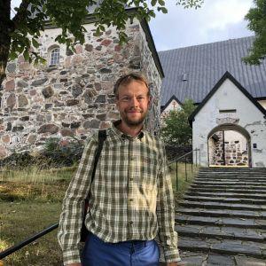 James Simpson, står framför kyrkan i Gamla Malmen i Pargas.