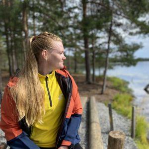 Liikunnanohjaaja Satu Suomalainen istuu nuotiopaikalla Luutalammin rannalla.