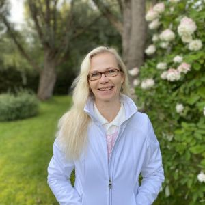 Suomen kasvukäytäverkoston johtaja Jaana Villanen pihalla hortensiapensaan edessä