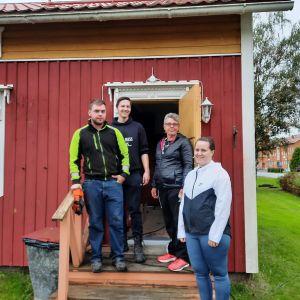 Fyra personer som står på en trappa till ett gammalt trähus.