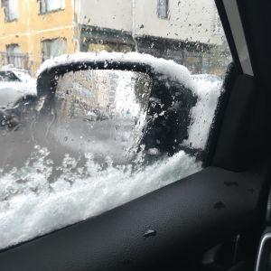Lumen peittämä auto ja näkymä.