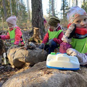 Neela Houni, Sointu Hämäläinen ja Iines Junnila leikkivät syksyisessä metsässä. Etualalla Junnila puhuu leikkipuhelimessa.