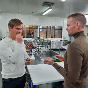En man bjuder en annan man på ett smakprov av mat.