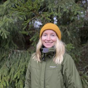 Vaaleatukkainen Jaana Santanen seisoo kuusten edessä keltainen pipo päässään ja vihreä takki yllään. Kuva otettu 25. lokakuuta 2021 Hämeenlinnan Rengossa.