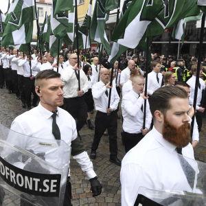 Nordiska motståndsrörelsen marscherar med grön-vita flaggor.