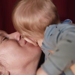 Soiva syli: äiti suukottaa lasta poskelle