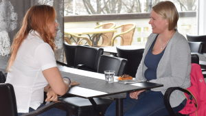 Paula Agge från Nurse Partners sitter vid ett bord och pratar med Daniela Laiho som sitter mittemot i samma bord.