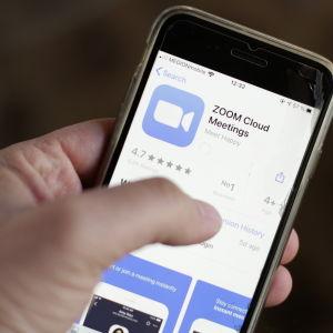 Mies pitelee älypuhelinta kädessään. Älypuhelimessa on Zoom-sovellus auki.